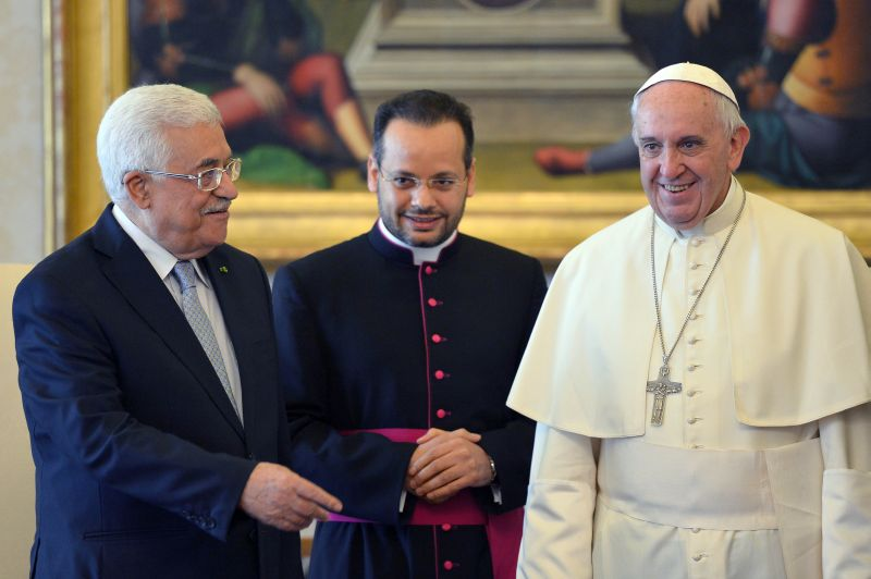 """Pope Francis smiles as he meets Palestinian leader Mahmoud Abbas during an audience at the Vatican Saturday, May 16, 2015. Pope Francis has praised Palestinian President Mahmoud Abbas as an """"angel of peace"""" during a meeting at the Vatican. Francis made the compliment Saturday during the traditional exchange of gifts at the end of an official audience in the Apostolic Palace. (Alberto Pizzoli/Pool Photo via AP)"""