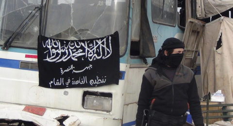 """A member of Islamist Syrian rebel group Jabhat al-Nusra mans a checkpoint on the border crossing between Syria and Jordan, which they claim to have taken control of, in Daraa December 26, 2013. Flag reads, """"There is no God but Allah, and Muhammad is his prophet. Al-Nusra front, al-Qaeda in the Levant"""". Picture taken December 26, 2013. REUTERS/Ammar Khassawneh (SYRIA - Tags: POLITICS CIVIL UNREST CONFLICT) - RTX16VW7"""